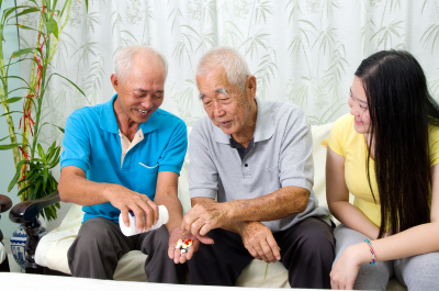 two senior man taking their medicine with their caregiver